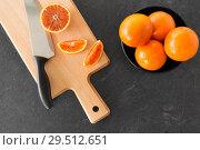 Купить «close up of oranges and knife on cutting board», фото № 29512651, снято 4 апреля 2018 г. (c) Syda Productions / Фотобанк Лори