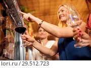 Купить «happy women pouring wine from dispenser at bar», фото № 29512723, снято 25 июня 2018 г. (c) Syda Productions / Фотобанк Лори