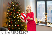 Купить «happy woman in red dress with christmas gift», фото № 29512967, снято 3 октября 2015 г. (c) Syda Productions / Фотобанк Лори