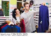 Купить «Couple examining various sports clothes in sports store», фото № 29523203, снято 22 ноября 2016 г. (c) Яков Филимонов / Фотобанк Лори