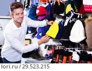 Купить «Man choosing new knit cap», фото № 29523215, снято 22 ноября 2016 г. (c) Яков Филимонов / Фотобанк Лори