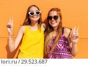 Купить «smiling teenage girls showing peace in summer», фото № 29523687, снято 19 июля 2018 г. (c) Syda Productions / Фотобанк Лори