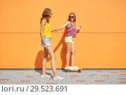 Купить «teenage girls riding skateboard on city street», фото № 29523691, снято 19 июля 2018 г. (c) Syda Productions / Фотобанк Лори