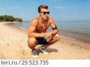 Купить «male runner with earphones and arm band on beach», фото № 29523735, снято 1 августа 2018 г. (c) Syda Productions / Фотобанк Лори