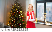 Купить «happy woman in red dress with christmas gifts», фото № 29523835, снято 3 октября 2015 г. (c) Syda Productions / Фотобанк Лори