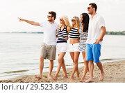Купить «friends in striped clothes walking along beach», фото № 29523843, снято 13 июля 2014 г. (c) Syda Productions / Фотобанк Лори