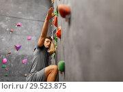Купить «young man exercising at indoor climbing gym», фото № 29523875, снято 2 марта 2017 г. (c) Syda Productions / Фотобанк Лори