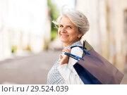 Купить «senior woman with shopping bags in city», фото № 29524039, снято 3 августа 2018 г. (c) Syda Productions / Фотобанк Лори
