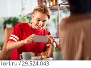 Купить «happy woman photographing cake at cafe», фото № 29524043, снято 7 августа 2018 г. (c) Syda Productions / Фотобанк Лори