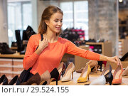 Купить «happy young woman choosing shoes at store», фото № 29524155, снято 22 сентября 2017 г. (c) Syda Productions / Фотобанк Лори