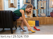 Купить «young woman trying high heeled shoes at store», фото № 29524159, снято 22 сентября 2017 г. (c) Syda Productions / Фотобанк Лори