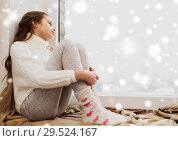 Купить «sad girl sitting on sill at home window in winter», фото № 29524167, снято 5 ноября 2016 г. (c) Syda Productions / Фотобанк Лори