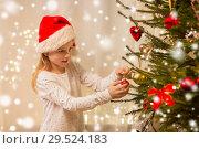 Купить «happy girl in santa hat decorating christmas tree», фото № 29524183, снято 22 декабря 2017 г. (c) Syda Productions / Фотобанк Лори