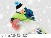 Купить «happy boy sliding on sled down snow hill in winter», фото № 29524327, снято 10 февраля 2018 г. (c) Syda Productions / Фотобанк Лори