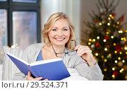 Купить «woman with glasses and book on christmas at home», фото № 29524371, снято 27 ноября 2015 г. (c) Syda Productions / Фотобанк Лори