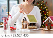 Купить «woman making gingerbread houses on christmas», фото № 29524435, снято 30 октября 2014 г. (c) Syda Productions / Фотобанк Лори