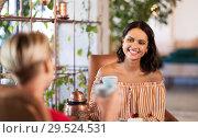 Купить «female friends drinking coffee and talking at cafe», фото № 29524531, снято 7 августа 2018 г. (c) Syda Productions / Фотобанк Лори