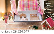 Купить «woman with gingerbread house parts on oven tray», фото № 29524647, снято 30 октября 2014 г. (c) Syda Productions / Фотобанк Лори