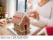 Купить «close up of woman making gingerbread house», фото № 29524651, снято 30 октября 2014 г. (c) Syda Productions / Фотобанк Лори