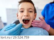 Купить «boy having teeth checkup at dental clinic», фото № 29524759, снято 22 апреля 2018 г. (c) Syda Productions / Фотобанк Лори