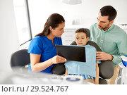 Купить «dentist showing tablet pc to kid at dental clinic», фото № 29524767, снято 22 апреля 2018 г. (c) Syda Productions / Фотобанк Лори