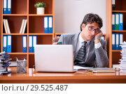 Young handsome businessman unhappy with excessive work. Стоковое фото, фотограф Elnur / Фотобанк Лори