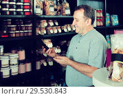 Купить «man looking at assortment of grocery products in shelves», фото № 29530843, снято 5 октября 2016 г. (c) Яков Филимонов / Фотобанк Лори