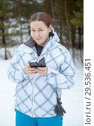 Портрет женщины со смартфоном в руках в зимнем лесу. Стоковое фото, фотограф Кекяляйнен Андрей / Фотобанк Лори