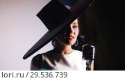 Купить «A woman in big black elegant hat stands behind the mic and emotional singing», видеоролик № 29536739, снято 16 января 2019 г. (c) Константин Шишкин / Фотобанк Лори