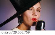 Купить «An attractive woman in big black elegant hat grabs the mic and starts singing. Bright lighting», видеоролик № 29536759, снято 17 декабря 2018 г. (c) Константин Шишкин / Фотобанк Лори