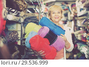 Купить «Adult female buyer choosing colour plaids in the textile store», фото № 29536999, снято 29 ноября 2017 г. (c) Яков Филимонов / Фотобанк Лори