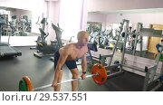 Купить «A young athletic man with a naked torso is engaged in physical work in the gym», видеоролик № 29537551, снято 22 января 2019 г. (c) Иван Карпов / Фотобанк Лори