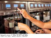 Купить «close up of woman with glass at wine dispenser», фото № 29537639, снято 25 июня 2018 г. (c) Syda Productions / Фотобанк Лори