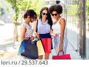 Купить «happy women showing shopping bags in city», фото № 29537643, снято 22 июля 2018 г. (c) Syda Productions / Фотобанк Лори