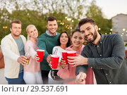 Купить «friends with drinks taking selfie at rooftop party», фото № 29537691, снято 2 сентября 2018 г. (c) Syda Productions / Фотобанк Лори