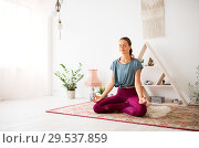 Купить «woman meditating in lotus pose at yoga studio», фото № 29537859, снято 21 июня 2018 г. (c) Syda Productions / Фотобанк Лори