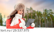 Купить «woman in fur hat with tablet pc over winter forest», фото № 29537975, снято 7 января 2017 г. (c) Syda Productions / Фотобанк Лори