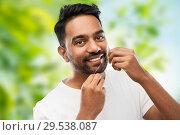 Купить «indian man with dental floss cleaning teeth», фото № 29538087, снято 27 октября 2018 г. (c) Syda Productions / Фотобанк Лори