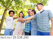 Купить «happy smiling friends stacking hands in park», фото № 29538243, снято 10 июня 2018 г. (c) Syda Productions / Фотобанк Лори