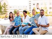 Купить «students with notebook waving hands outdoors», фото № 29538251, снято 10 июня 2018 г. (c) Syda Productions / Фотобанк Лори