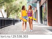 Купить «teenage girls with short skateboards in city», фото № 29538303, снято 19 июля 2018 г. (c) Syda Productions / Фотобанк Лори
