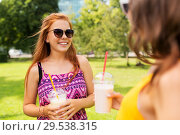 teenage girls with milk shakes at summer park. Стоковое фото, фотограф Syda Productions / Фотобанк Лори