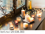 Купить «candles burning on window sill with garland lights», фото № 29538383, снято 13 января 2018 г. (c) Syda Productions / Фотобанк Лори