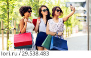 Купить «women with shopping bags taking selfie in city», фото № 29538483, снято 22 июля 2018 г. (c) Syda Productions / Фотобанк Лори