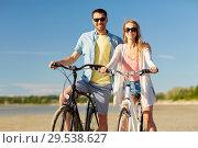 Купить «happy young couple riding bicycles at seaside», фото № 29538627, снято 23 июля 2017 г. (c) Syda Productions / Фотобанк Лори