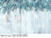 Купить «Winter Christmas and New year background. Blue fir tree branches with winter snowflakes on the wooden background», фото № 29539095, снято 8 мая 2017 г. (c) Зезелина Марина / Фотобанк Лори