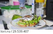 Купить «Healthy breakfast. Making a sandwich with fried egg and avocado. Pouring the sauce», видеоролик № 29539407, снято 25 мая 2020 г. (c) Константин Шишкин / Фотобанк Лори
