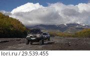 Купить «Japanese SUV driving on mountain road on dry river in direction of volcano», видеоролик № 29539455, снято 27 сентября 2018 г. (c) А. А. Пирагис / Фотобанк Лори