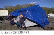 Купить «Group of rescuers setting up an army field tent, deploy campground on windy day», видеоролик № 29539471, снято 2 октября 2018 г. (c) А. А. Пирагис / Фотобанк Лори