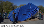 Купить «Group of rescuers setting up an army field tent, deploy campground on windy day», видеоролик № 29539475, снято 2 октября 2018 г. (c) А. А. Пирагис / Фотобанк Лори